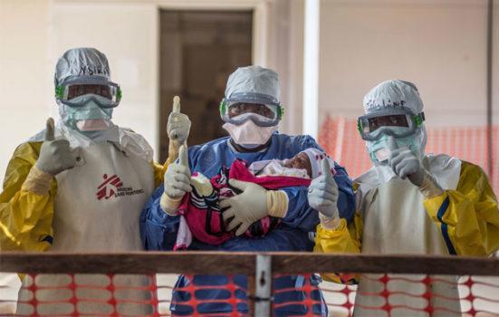 Den lille pige Nubia bliver her båret ud fra et hospital i Guinea, efter at hun har overlevet ebola